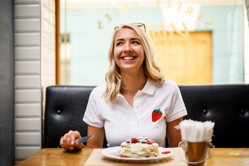 Woman smiling and eating pancakes