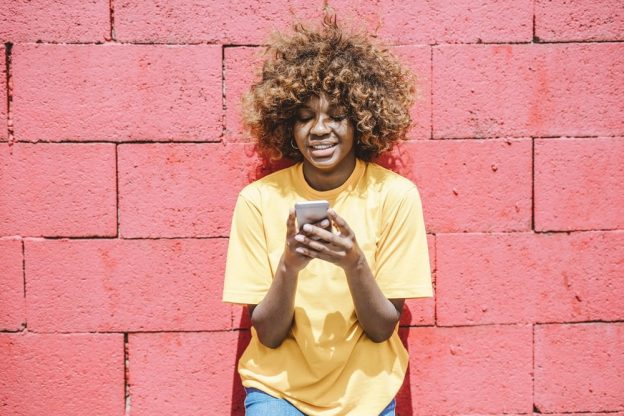 woman-in-yellow-shirt-holding-cellular-phone