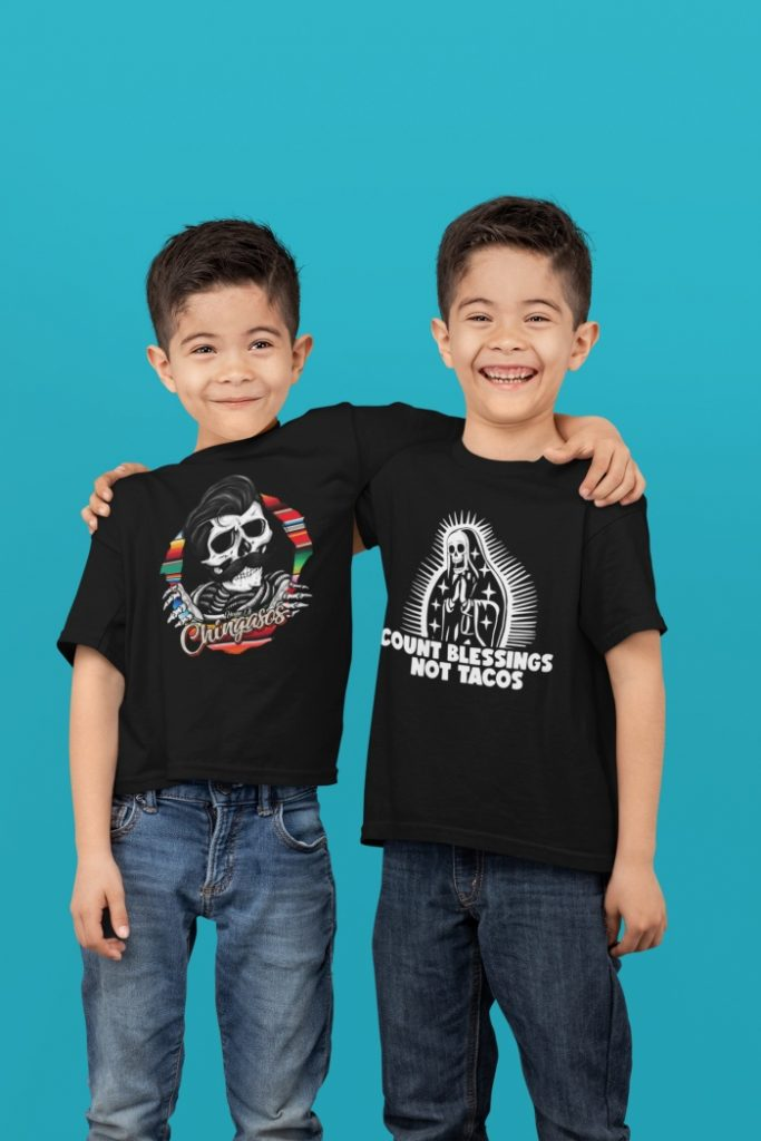 Two boys smiling wearing House of Chingasos t-shirts