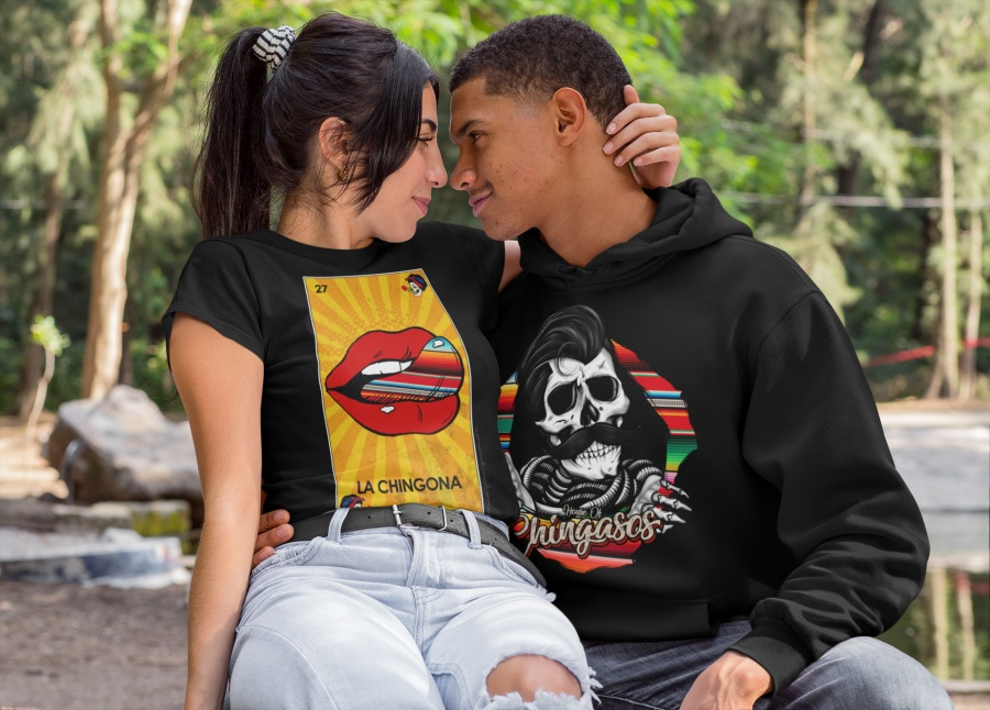 A couple snuggling and wearing House of Chingasos t-shirts