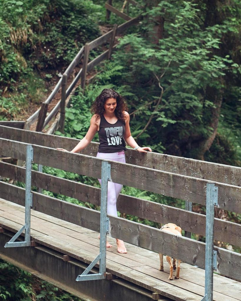 A woman hikes in a tofu love tank top