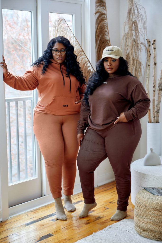 Kimberly and Keyondra standing together wearing coordinating sweatsuits