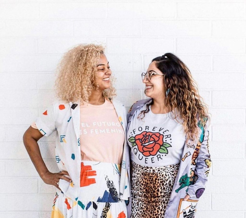 Two women wear Passionfruit t-shirts and smile